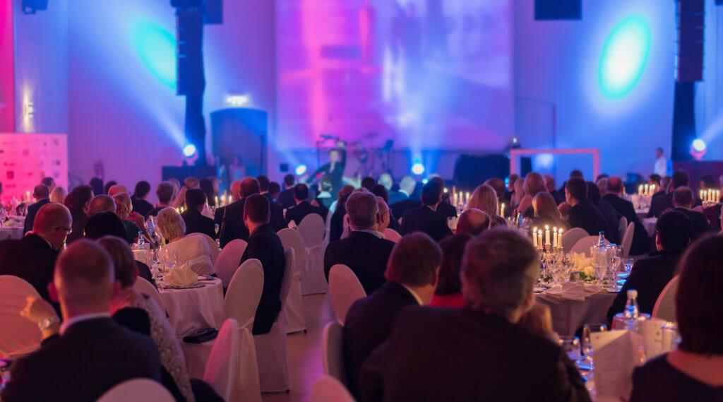 Gäste an Tischen mit Bühne im Hintergrund während einer Veranstaltung
