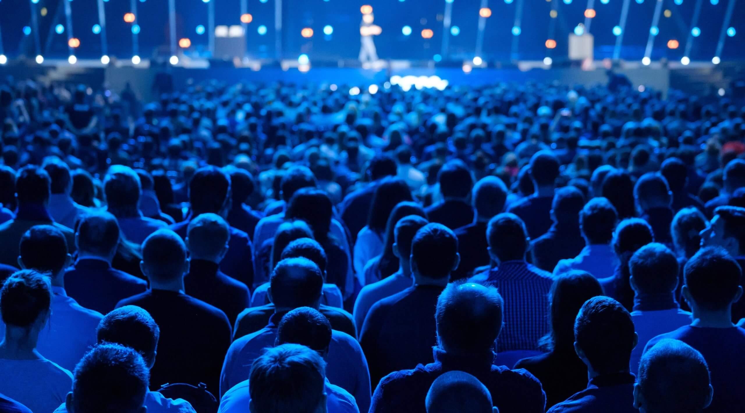 Sitzendes Publikum während eines Vortrags mit Bühne und Redner