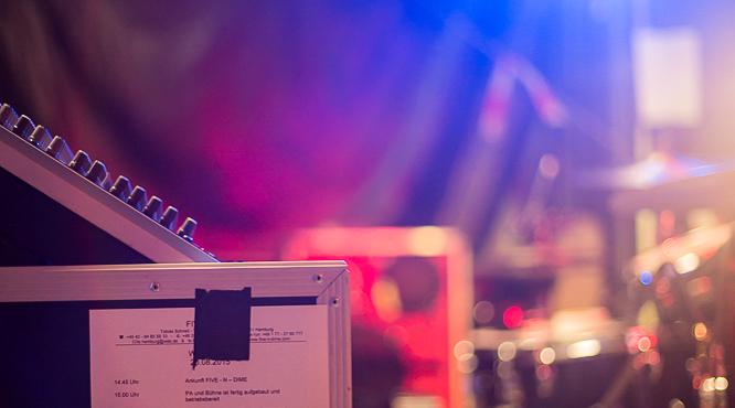 Case mit aufgeklebter Running-Order auf Bühne mit Equipment im Hintergrund
