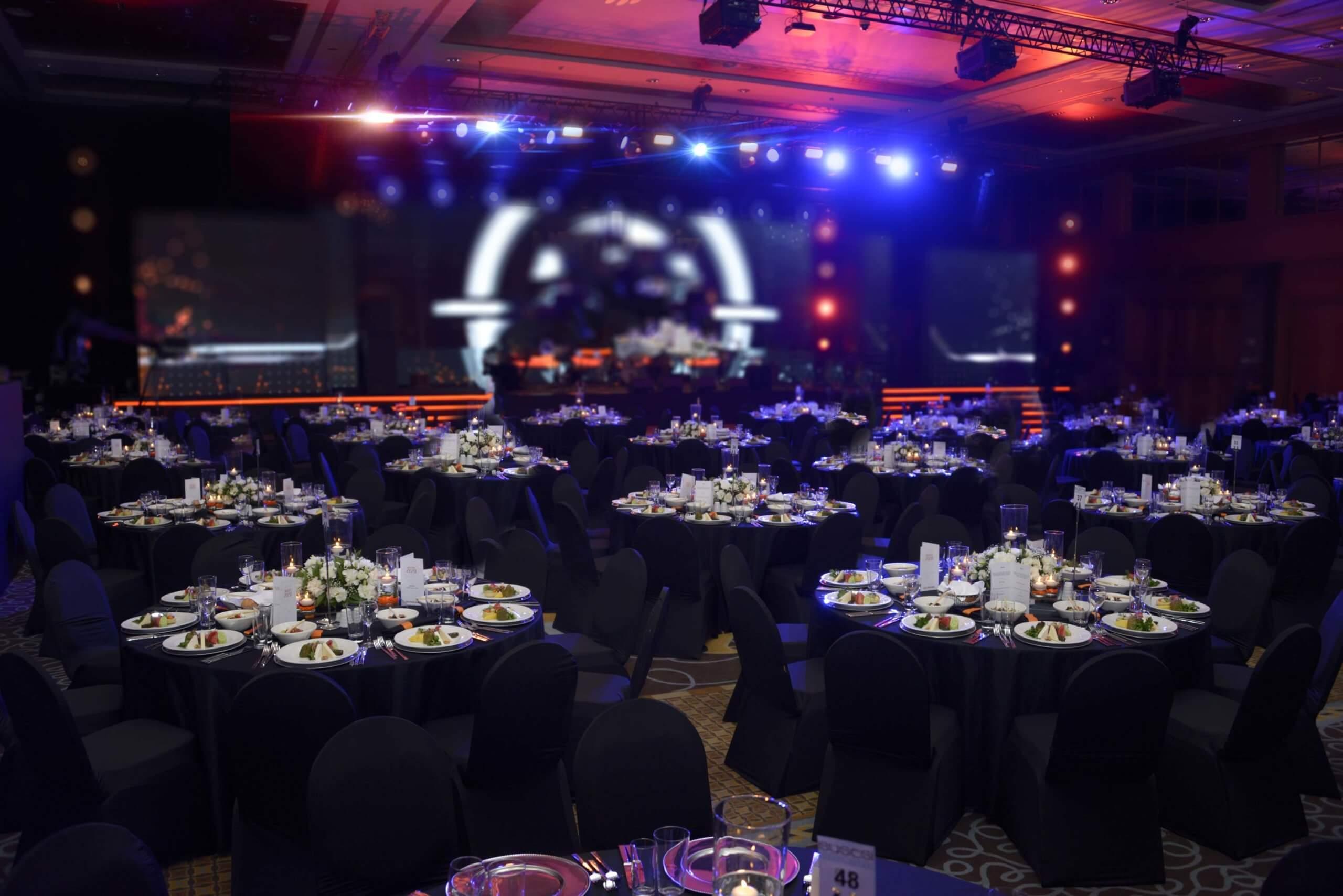 Festlich gedeckte Tische mit Bühne im Hintergrund