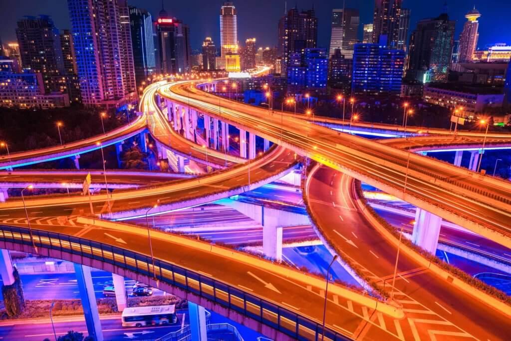 Mehrere leere, beleuchtete Straßen und Brücken mit Skyline einer Stadt im Hintergrund