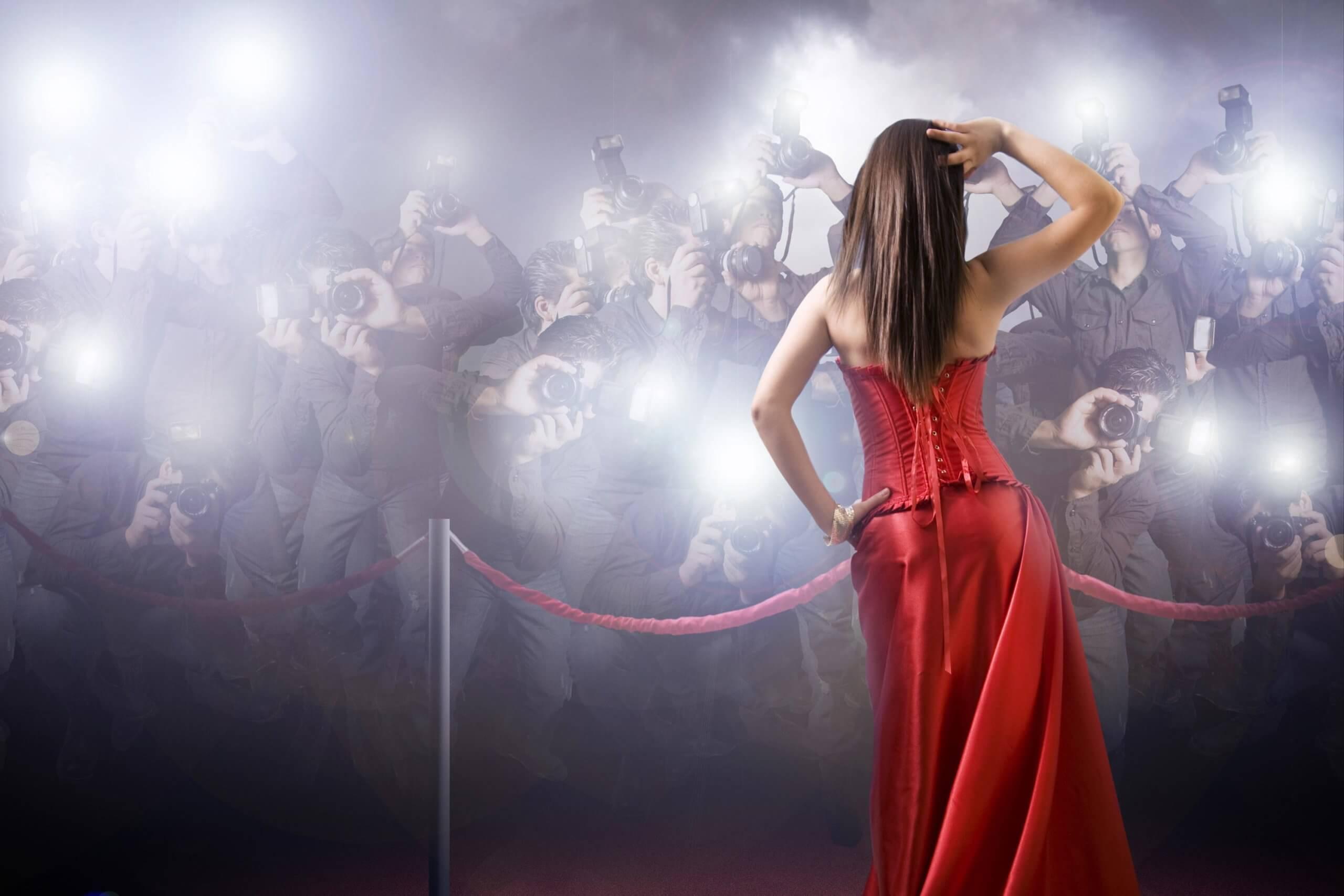 Frau auf rotem Teppich wird von vielen Fotografen fotografiert