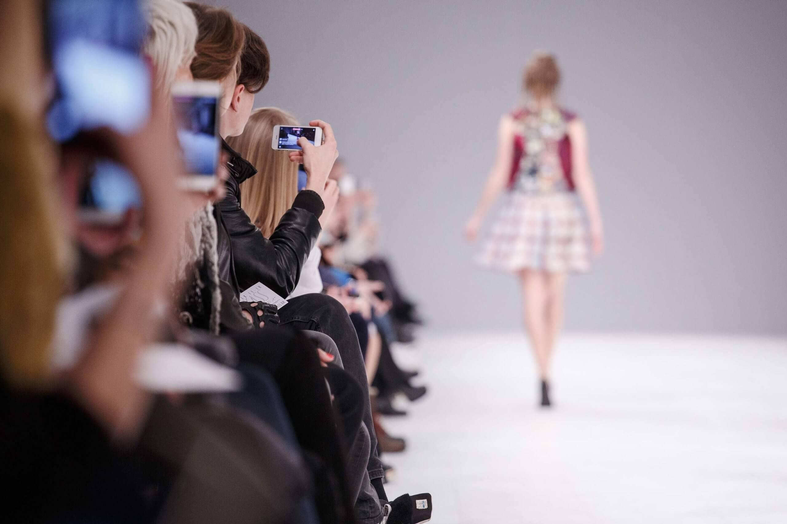 Publikum, dass einem Model auf dem Laufsteg hinterher schaut