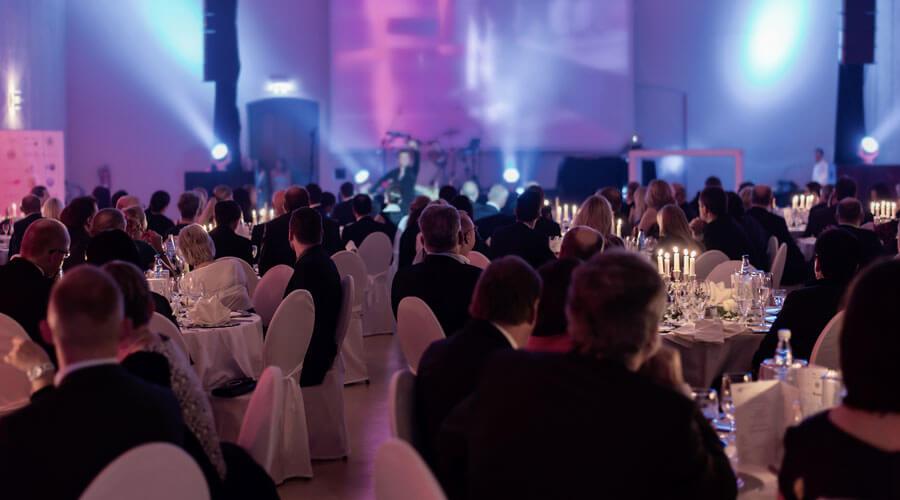 Festlich gedeckte Tische mit Gästen und Bühne im Hintergrund