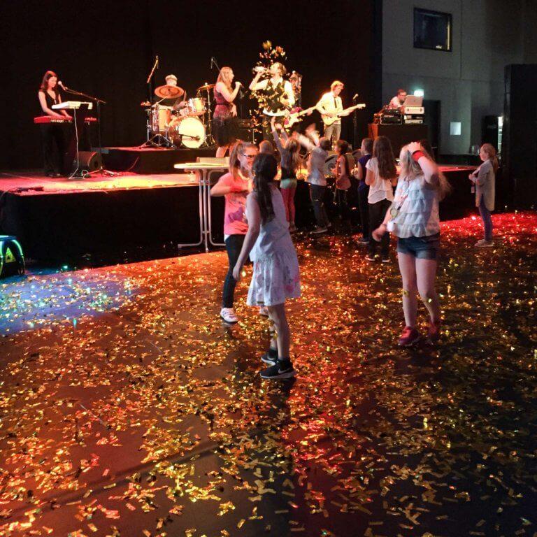 Tanzende Gäste vor Bühne mit Band und Glitzer-Konfetti