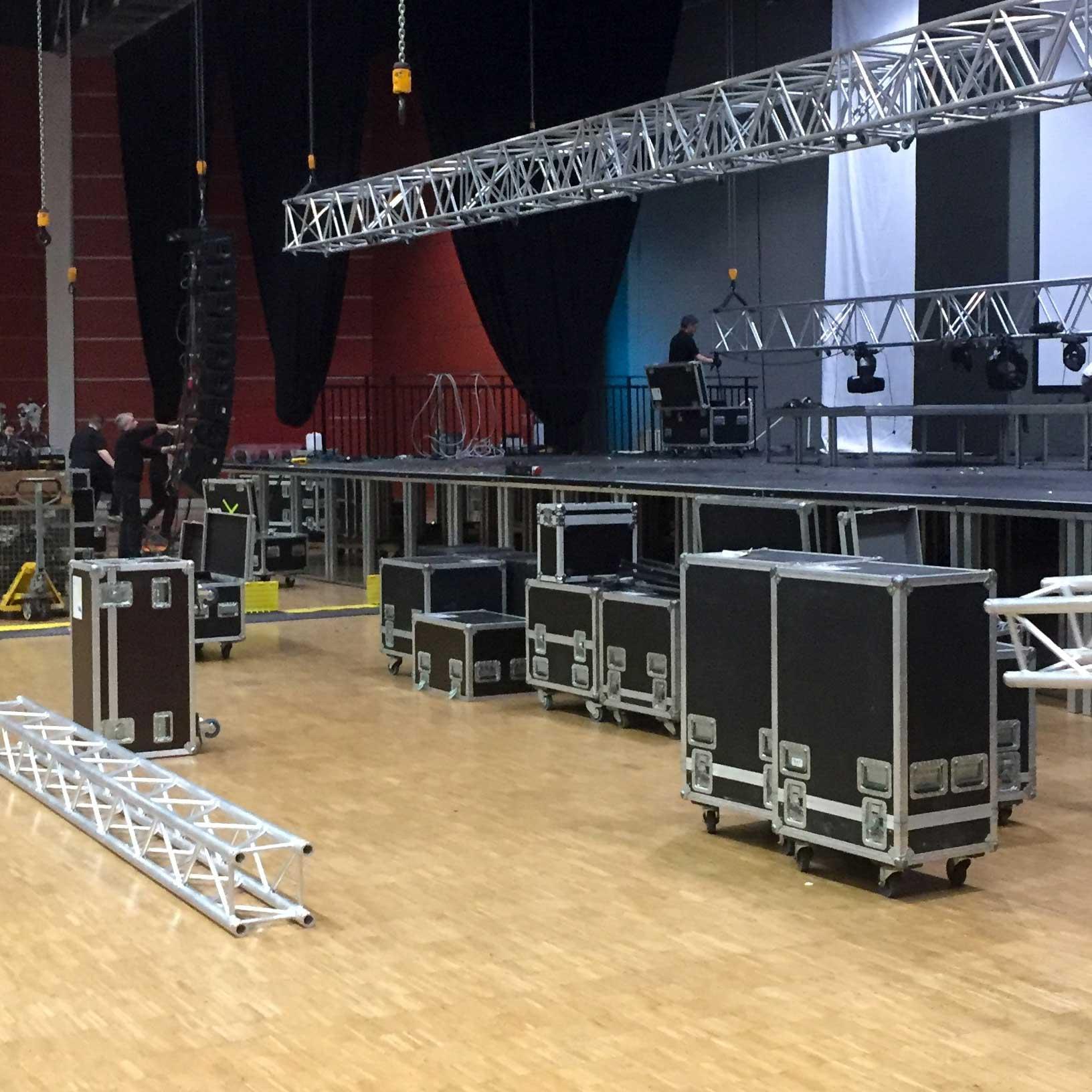 Roadies beim Aufbau von Equipment auf einer Bühne