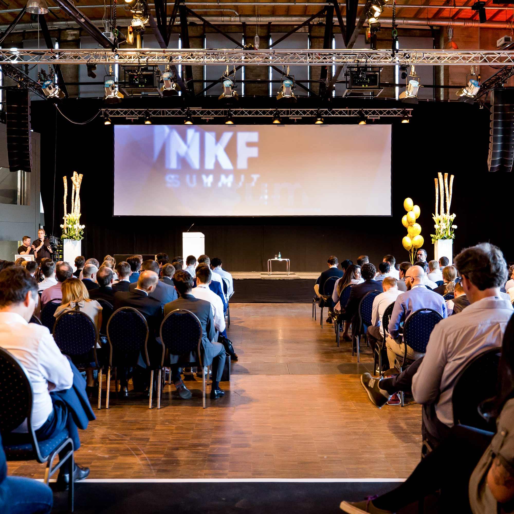 Vortragshalle mit sitzenden Besuchern und Bühne mit großer Leinwand