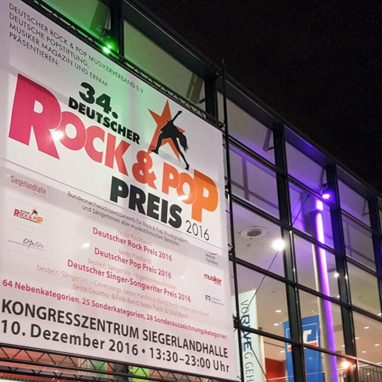 Großes Plakat mit Veranstaltungsankündigung am Traversensystem an der Aussenfront der Halle