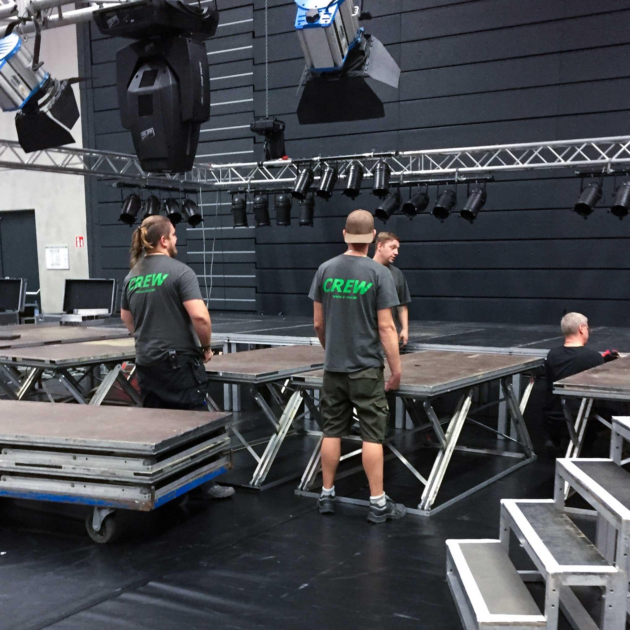 Roadies und Bühnentechniker bauen eine Bühne auf