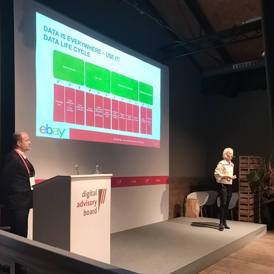 Zwei Speaker auf einer Vortragsbühne vor großer Szene