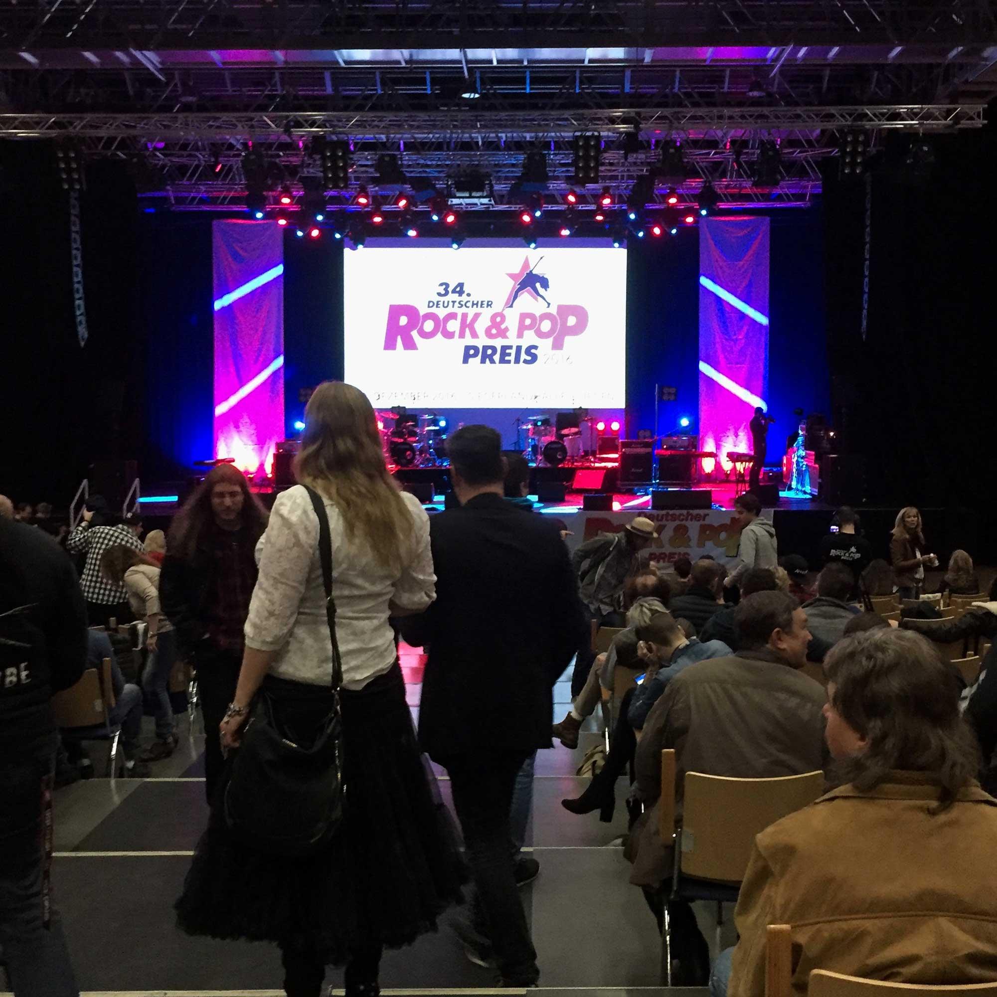 Mittelgang des Publikumsbereichs einer Konzerthalle mit Publikum und Draufsicht auf beleuchtete Konzertbühne
