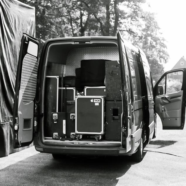 Geöffneter Tourvan neben einer Bühne mit geladenem Equipment
